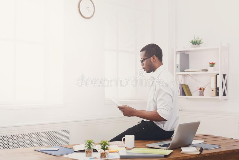 Συγκεντρωμένος μαύρος επιχειρηματίας στο σύγχρονο γραφείο, εργασία με την ταμπλέτα στοκ φωτογραφίες