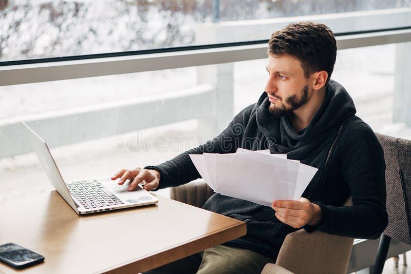 Συγκεντρωμένος νέος γενειοφόρος επιχειρηματίας που φορά το μαύρο αστικό καφέ lap-top μπλουζών λειτουργώντας στοκ εικόνα με δικαίωμα ελεύθερης χρήσης