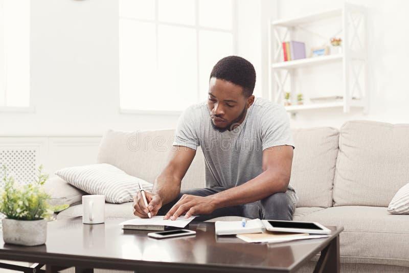 Συγκεντρωμένος νεαρός άνδρας που προετοιμάζεται για τους διαγωνισμούς στο σπίτι στοκ εικόνες