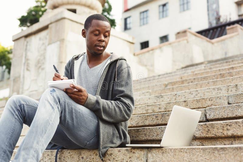 Συγκεντρωμένος σπουδαστής αφροαμερικάνων που μελετά με το lap-top και το σημειωματάριο υπαίθρια στοκ φωτογραφίες με δικαίωμα ελεύθερης χρήσης