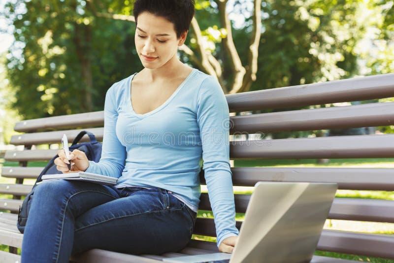 Συγκεντρωμένος σπουδαστής που μελετά με το lap-top και το σημειωματάριο υπαίθρια στοκ φωτογραφίες με δικαίωμα ελεύθερης χρήσης