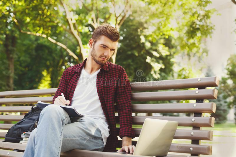 Συγκεντρωμένος σπουδαστής που μελετά με το lap-top και το σημειωματάριο υπαίθρια στοκ φωτογραφία με δικαίωμα ελεύθερης χρήσης
