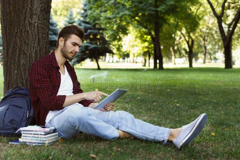 Συγκεντρωμένος σπουδαστής που προετοιμάζεται για το διαγωνισμό στο πάρκο στοκ εικόνες