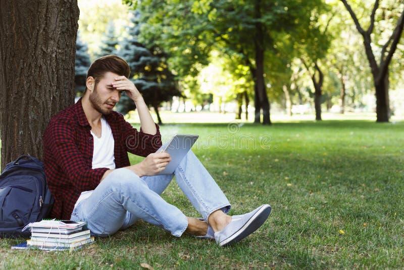 Συγκεντρωμένος σπουδαστής που προετοιμάζεται για το διαγωνισμό στο πάρκο στοκ εικόνα με δικαίωμα ελεύθερης χρήσης
