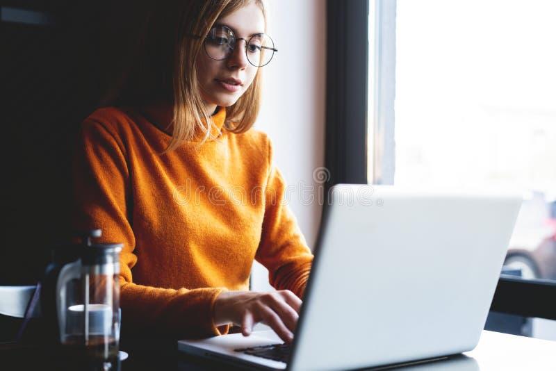 Συγκεντρωμένος στην εργασία Βέβαια νέα γυναίκα στην έξυπνη περιστασιακή ένδυση που εργάζεται στο lap-top καθμένος κοντά στο παράθ στοκ φωτογραφίες