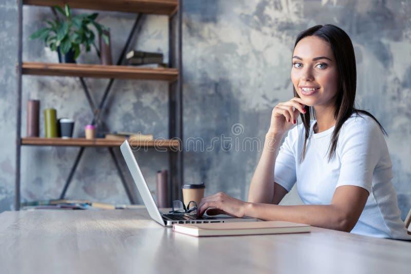 Συγκεντρωμένος στην εργασία Βέβαια νέα γυναίκα στην έξυπνη περιστασιακή ένδυση που εργάζεται στο lap-top καθμένος κοντά στο παράθ στοκ εικόνες