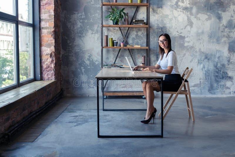 Συγκεντρωμένος στην εργασία Βέβαια νέα γυναίκα στην έξυπνη περιστασιακή ένδυση που εργάζεται στο lap-top καθμένος κοντά στο παράθ στοκ φωτογραφία με δικαίωμα ελεύθερης χρήσης