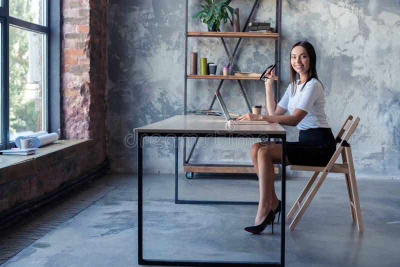Συγκεντρωμένος στην εργασία Βέβαια νέα γυναίκα στην έξυπνη περιστασιακή ένδυση που εργάζεται στο lap-top καθμένος κοντά στο παράθ στοκ εικόνες με δικαίωμα ελεύθερης χρήσης