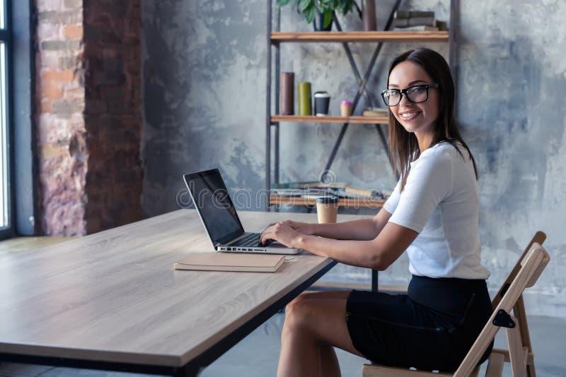 Συγκεντρωμένος στην εργασία Βέβαια νέα γυναίκα στην έξυπνη περιστασιακή ένδυση που εργάζεται στο lap-top καθμένος κοντά στο παράθ στοκ φωτογραφίες με δικαίωμα ελεύθερης χρήσης