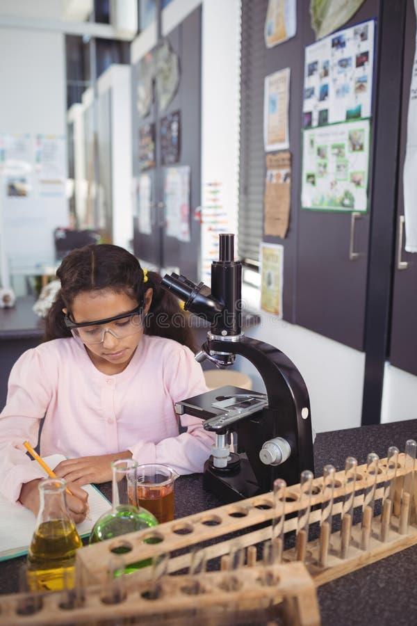 Συγκεντρωμένος στοιχειώδης σπουδαστής που γράφει στο βιβλίο από το μικροσκόπιο στο εργαστήριο στοκ φωτογραφία με δικαίωμα ελεύθερης χρήσης