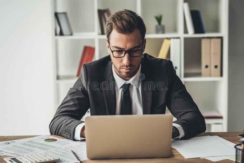 συγκεντρωμένος όμορφος επιχειρηματίας που εργάζεται με το lap-top στοκ εικόνα