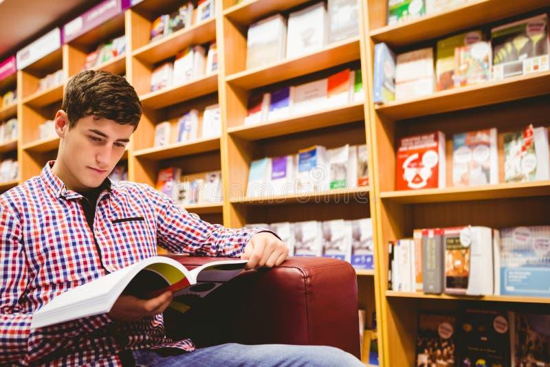 Συγκεντρωμένο βιβλίο ανάγνωσης νεαρών άνδρων στη βιβλιοθήκη στοκ φωτογραφία με δικαίωμα ελεύθερης χρήσης