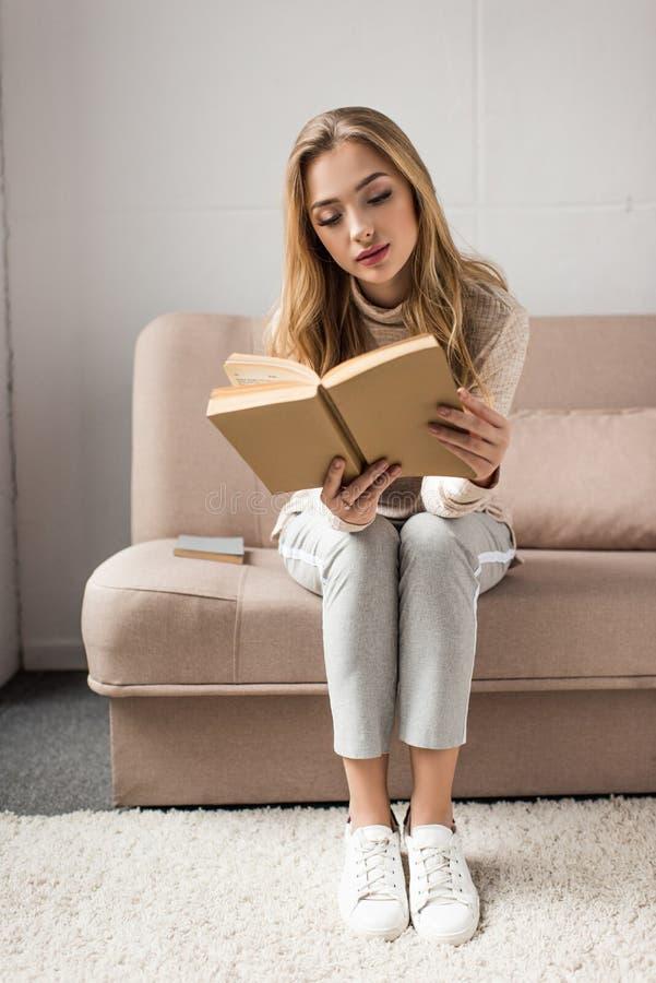 συγκεντρωμένο νέο βιβλίο ανάγνωσης γυναικών στον άνετο καναπέ στοκ φωτογραφία με δικαίωμα ελεύθερης χρήσης