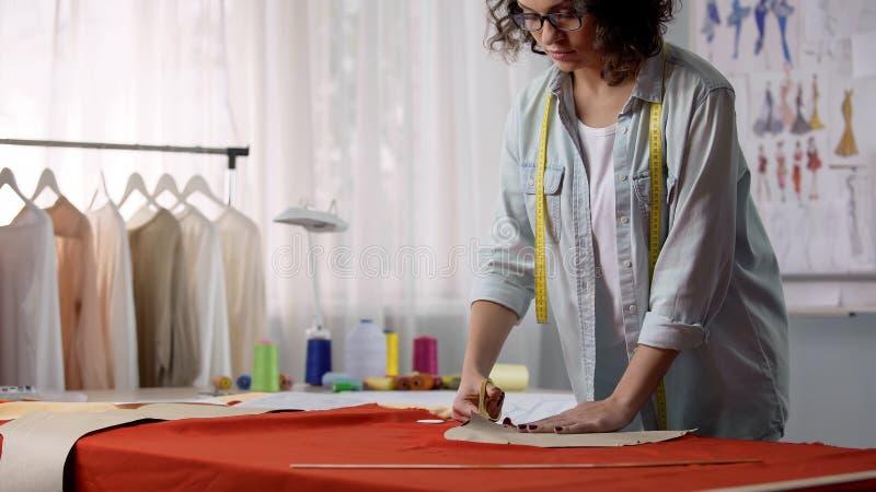 Συγκεντρωμένο τέμνον κομμάτι προς κατεργασία ραφτών από το ύφασμα, γυναίκα που λειτουργεί στο ατελιέ στοκ εικόνα