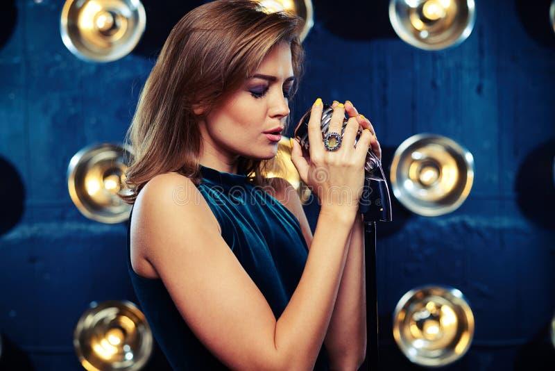 Συγκεντρωμένο όμορφο νέο τραγούδι γυναικών σε ένα αναδρομικό μικρόφωνο στοκ εικόνες