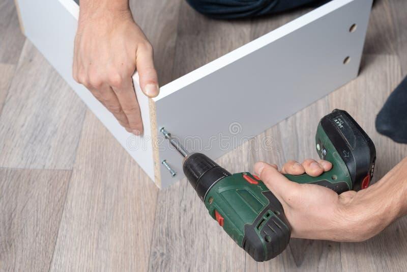 Συγκεντρώνοντας έπιπλα το άτομο συλλέγει τα έπιπλα με ένα κατσαβίδι στο πάτωμα του σπιτιού στοκ εικόνες με δικαίωμα ελεύθερης χρήσης