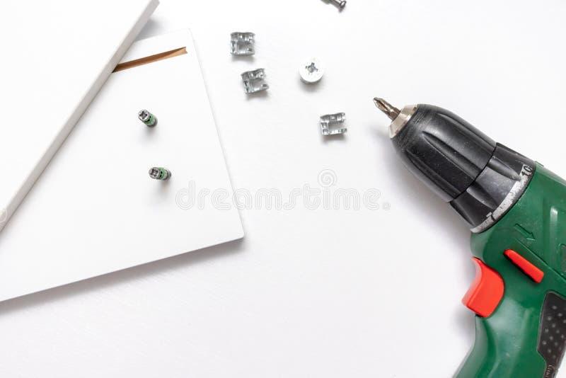 Συγκεντρώνοντας τα έπιπλα από το χαρτόνι, που χρησιμοποιεί ένα ασύρματο κατσαβίδι, το επίπεδο βρέθηκε στοκ εικόνα