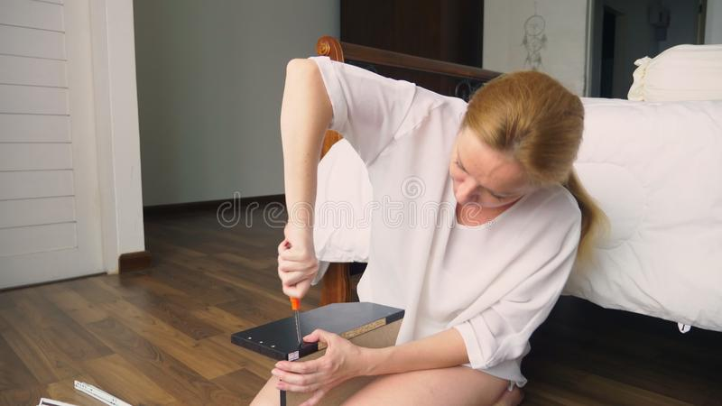 Συγκεντρώνοντας τα έπιπλα στο σπίτι, μια νοικοκυρά συγκεντρώνει ένα γραφείο υπολογιστών χρησιμοποιώντας τα εργαλεία χεριών στοκ φωτογραφίες