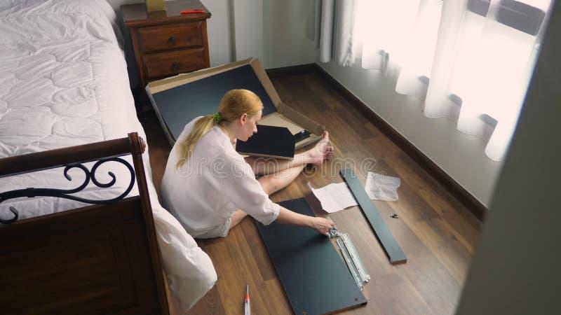 Συγκεντρώνοντας τα έπιπλα στο σπίτι, μια νοικοκυρά συγκεντρώνει ένα γραφείο υπολογιστών χρησιμοποιώντας τα εργαλεία χεριών στοκ εικόνες με δικαίωμα ελεύθερης χρήσης