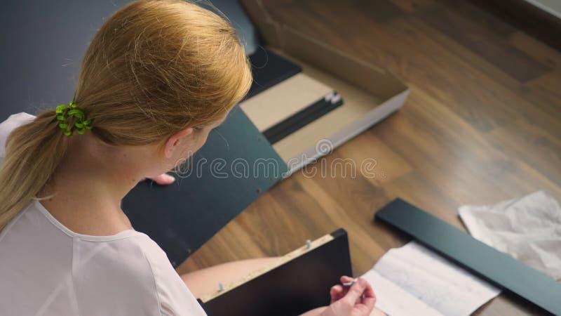 Συγκεντρώνοντας τα έπιπλα στο σπίτι, μια νοικοκυρά συγκεντρώνει ένα γραφείο υπολογιστών χρησιμοποιώντας τα εργαλεία χεριών στοκ εικόνες