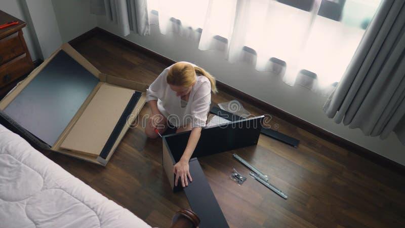 Συγκεντρώνοντας τα έπιπλα στο σπίτι, μια νοικοκυρά συγκεντρώνει ένα γραφείο υπολογιστών χρησιμοποιώντας τα εργαλεία χεριών στοκ φωτογραφία