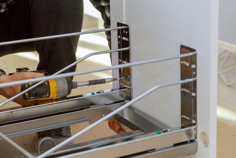 Συγκεντρώνοντας woodworker επίπλων που βιδώνει χρησιμοποιώντας ένα ασύρματο δοχείο απορριμάτων συρταριών κατσαβιδιών στην κουζίνα στοκ εικόνες με δικαίωμα ελεύθερης χρήσης