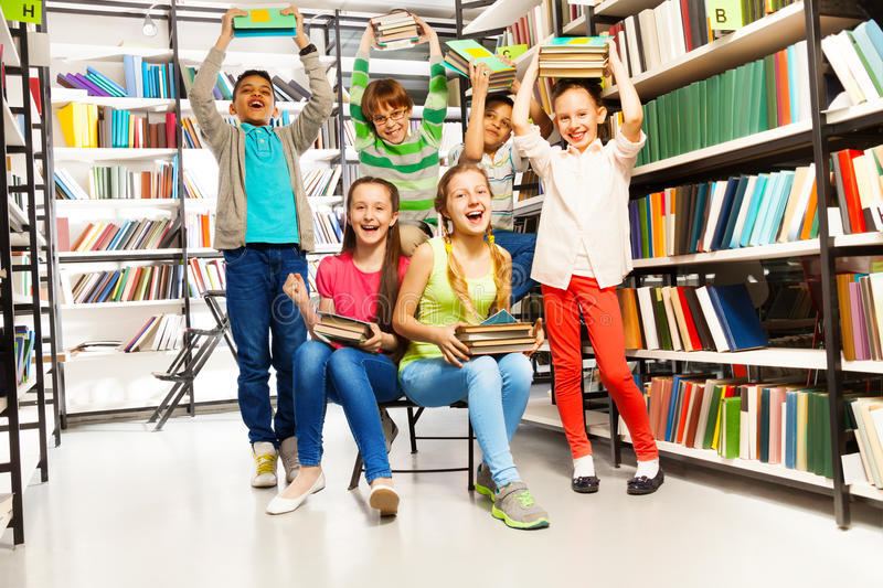 Συγκινημένα ευτυχή γελώντας παιδιά στη βιβλιοθήκη στοκ εικόνες