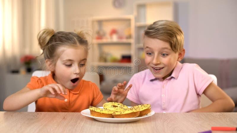 Συγκινημένα κορίτσι και αγόρι που εξετάζουν τα κίτρινα donuts, ανθυγειινό αλλά νόστιμο πρόχειρο φαγητό, τρόφιμα στοκ εικόνα