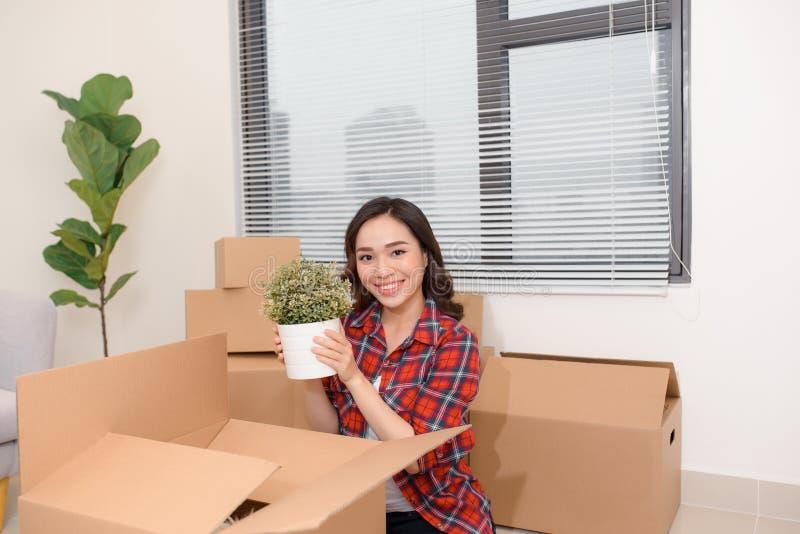 Συγκινημένα νέα ασιατικά κιβώτια χαρτοκιβωτίων γυναικών ανοίγοντας με το άνετο σπίτι στοκ εικόνα