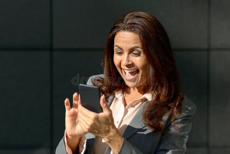 Συγκινημένη ενήλικη γυναίκα που χρησιμοποιεί το smartphone στοκ εικόνα με δικαίωμα ελεύθερης χρήσης