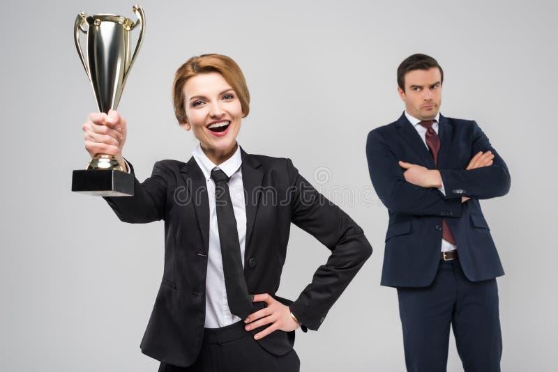 συγκινημένη επιχειρηματίας με το βραβείο και επιχειρηματίας πίσω, στοκ φωτογραφίες