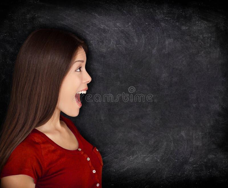 Συγκινημένη ευτυχής γυναίκα από τον πίνακα/τον πίνακα κιμωλίας στοκ εικόνες