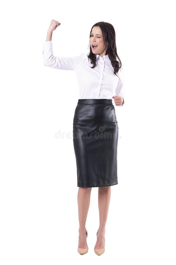 Συγκινημένη ευτυχής νέα επιχειρησιακή γυναίκα που γιορτάζει και που λυγίζει bicep το κλείσιμο του ματιού στη κάμερα στοκ φωτογραφία