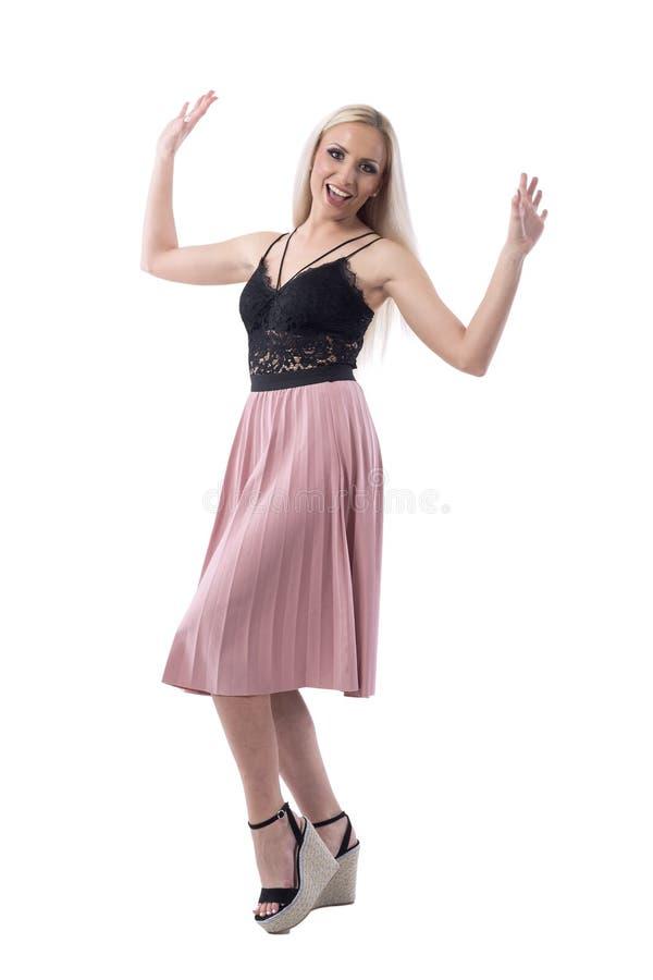 Συγκινημένη εύθυμη νέα ξανθή μοντέρνη μοντέρνη γυναίκα με τα αυξημένα όπλα στοκ φωτογραφίες