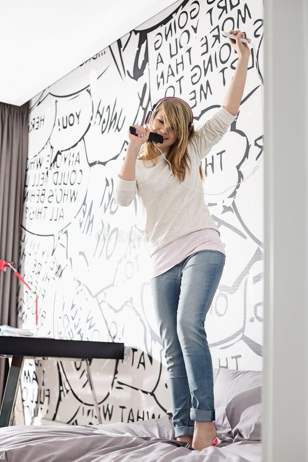 Συγκινημένη μουσική ακούσματος κοριτσιών τραγουδώντας στη βούρτσα γηα τα μαλλιά στο σπίτι στοκ εικόνα με δικαίωμα ελεύθερης χρήσης