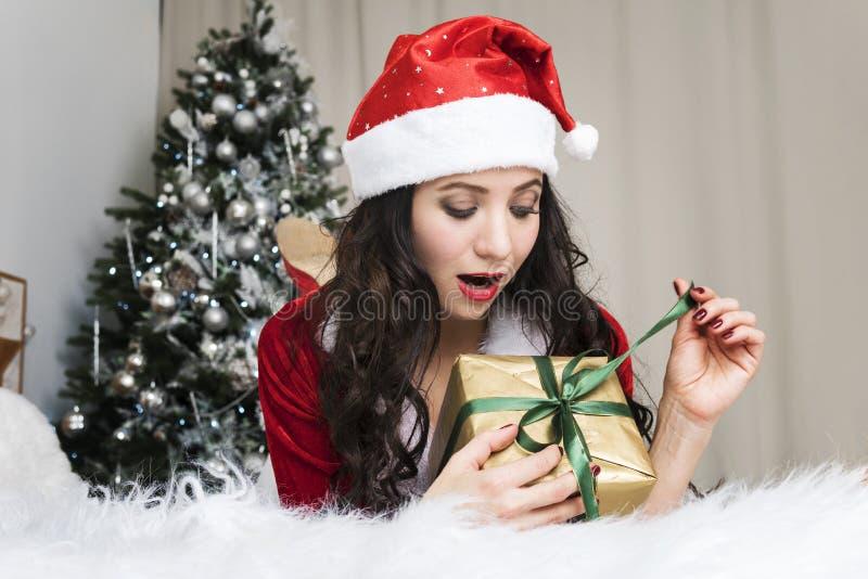 Συγκινημένη νέα γυναίκα που ανοίγει ένα δώρο Χριστουγέννων Το χαριτωμένο κορίτσι σε ένα κοστούμι Άγιου Βασίλη εξαπολύει μια κορδέ στοκ φωτογραφία με δικαίωμα ελεύθερης χρήσης
