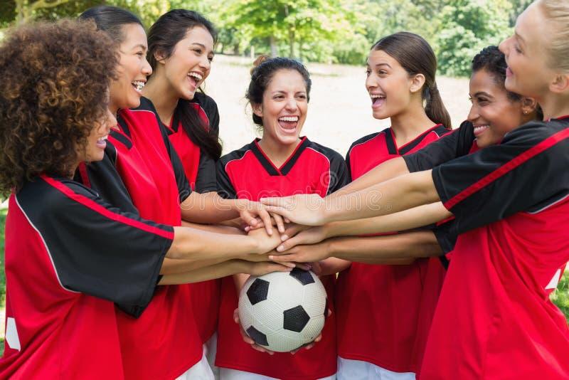 Συγκινημένη ομάδα ποδοσφαίρου που συσσωρεύει τα χέρια στη σφαίρα στοκ εικόνες