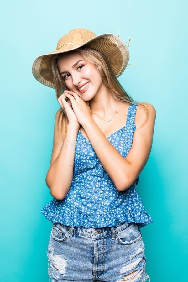 Συγκινημένη χαριτωμένη νέα γυναίκα στη στάση καπέλων αχύρου που απομονώνεται πέρα από το μπλε υπόβαθρο στοκ φωτογραφίες