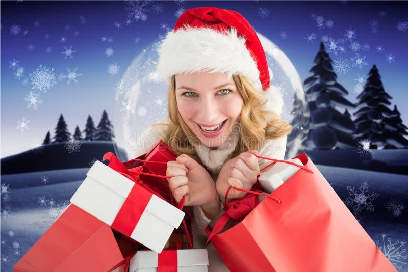 Συγκινημένη όμορφη γυναίκα στις τσάντες δώρων εκμετάλλευσης καπέλων santa στοκ φωτογραφίες με δικαίωμα ελεύθερης χρήσης