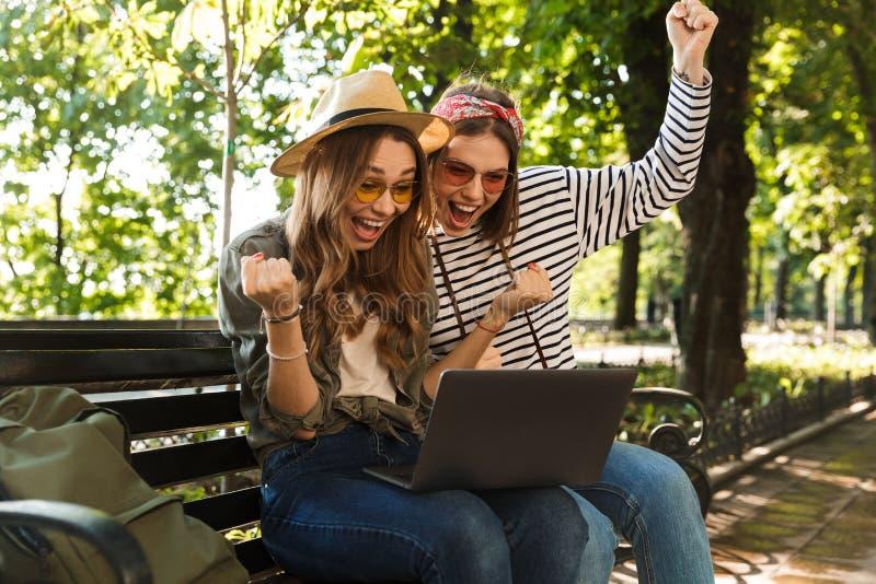 Συγκινημένοι ευτυχείς γυναικείοι φίλοι που κάθονται υπαίθρια χρησιμοποιώντας το φορητό προσωπικό υπολογιστή στοκ φωτογραφία