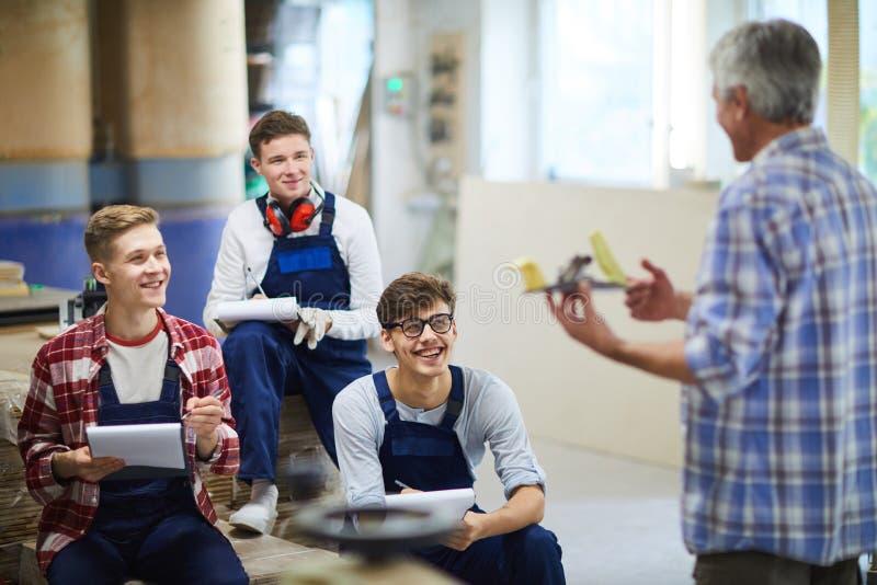 Συγκινημένοι σπουδαστές ξυλουργικής που γελούν κατά τη διάρκεια της ενδιαφέρουσας κατηγορίας στοκ φωτογραφίες