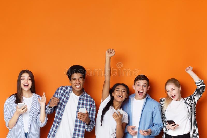 Συγκινημένοι φίλοι με τα τηλέφωνα που κραυγάζουν και που γιορτάζουν την επιτυχία στοκ φωτογραφία με δικαίωμα ελεύθερης χρήσης