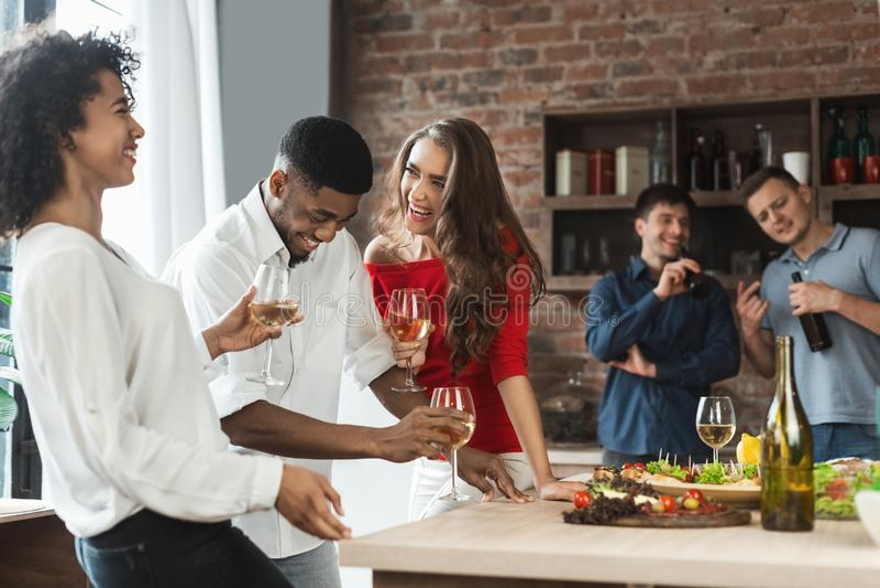 Συγκινημένοι φίλοι που πίνουν και που γελούν στην κουζίνα στοκ εικόνα