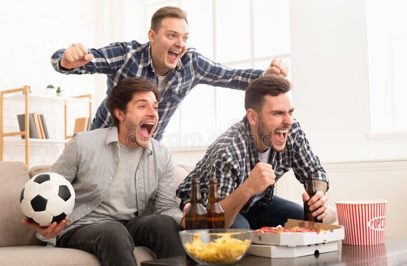 Συγκινημένοι φίλοι που προσέχουν τον αγώνα ποδοσφαίρου και να φωνάξει στοκ φωτογραφίες