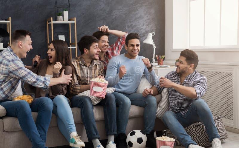 Συγκινημένοι φίλοι που προσέχουν τον αγώνα ποδοσφαίρου στο σπίτι στοκ εικόνα