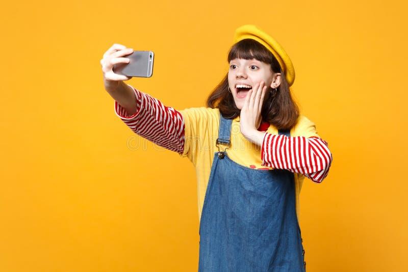 Συγκινημένος έφηβος κοριτσιών γαλλικό beret, να κάνει τζιν sundress selfie που πυροβολείται στο κινητό τηλέφωνο, που βάζει το χέρ στοκ εικόνα