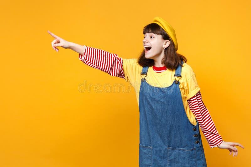 Συγκινημένος έφηβος κοριτσιών γαλλικό beret, τζιν sundress που δείχνει το αντίχειρα κατά μέρος και που κρατά στοματικό ανοικτό απ στοκ φωτογραφίες με δικαίωμα ελεύθερης χρήσης