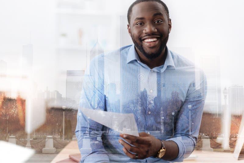 Συγκινημένος αφροαμερικάνος που κρατά ένα έγγραφο στο χέρι του στοκ φωτογραφία με δικαίωμα ελεύθερης χρήσης