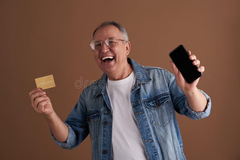 Συγκινημένος ενήλικος που γελά παρουσιάζοντας το smartphone και χρυσή κάρτα του στοκ φωτογραφία