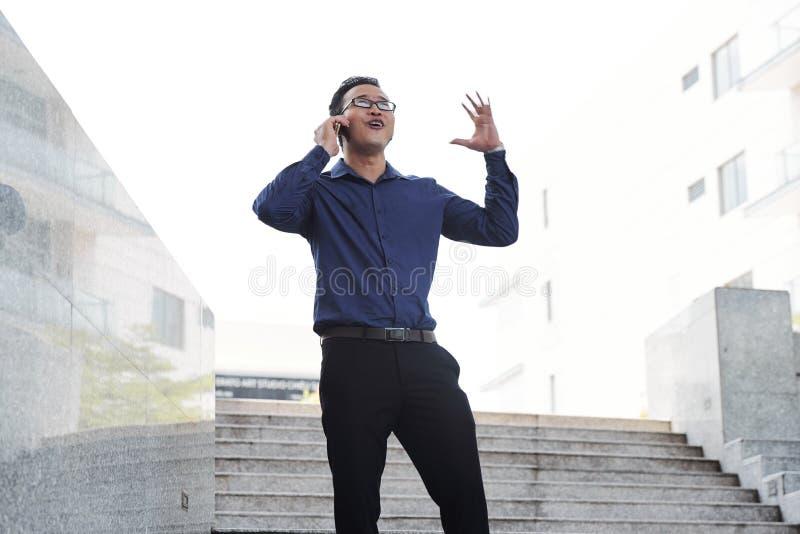 Συγκινημένος επιχειρηματίας που μιλά στο τηλέφωνο στοκ εικόνες